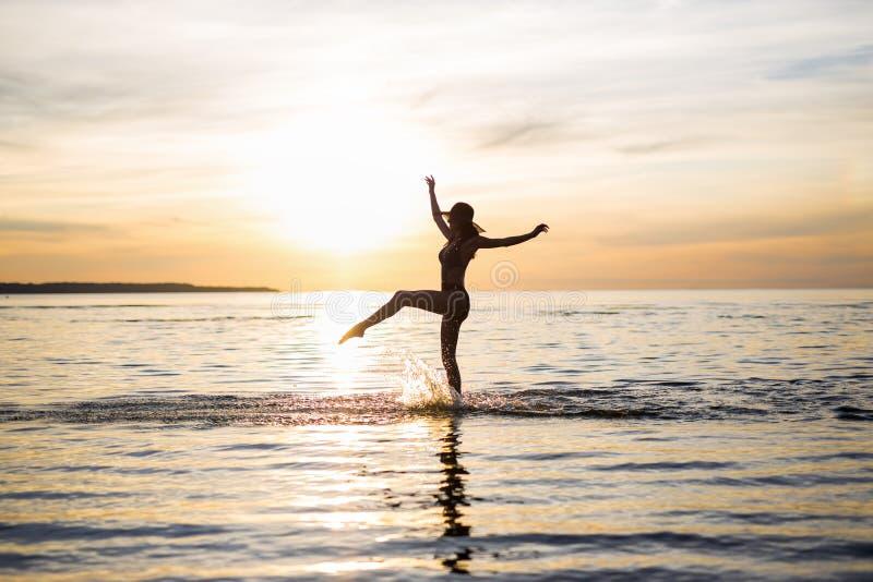 Silueta de la muchacha atractiva delgada en bikini que camina en la playa foto de archivo