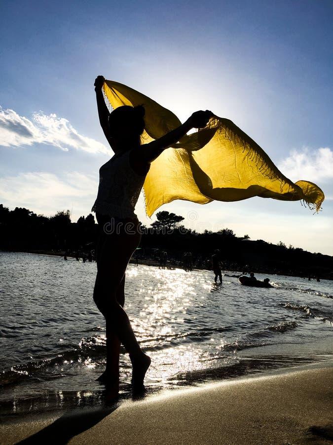 Silueta de la muchacha con la bufanda amarilla bajo puesta del sol foto de archivo libre de regalías