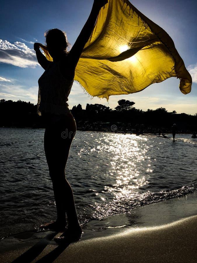 Silueta de la muchacha con la bufanda amarilla bajo puesta del sol fotografía de archivo