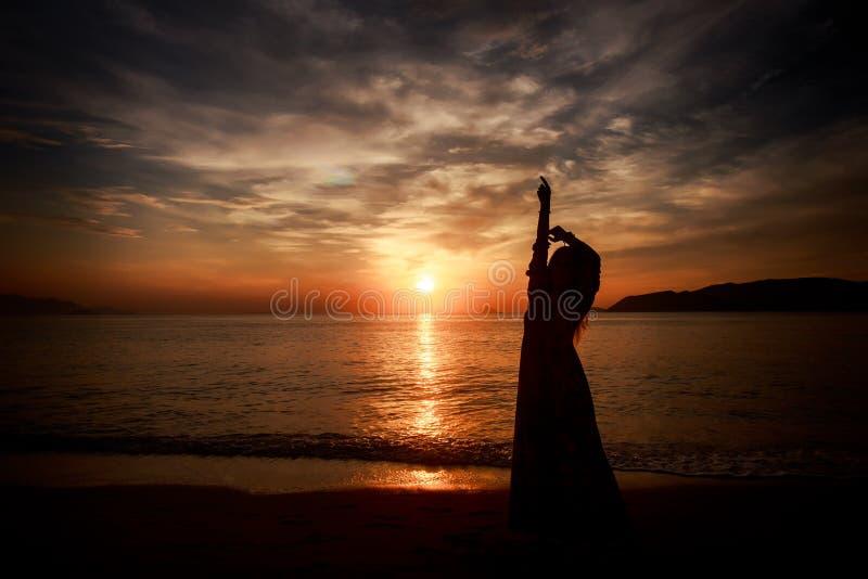 silueta de la muchacha delgada adentro de largo contra salida del sol sobre el mar imagen de archivo libre de regalías