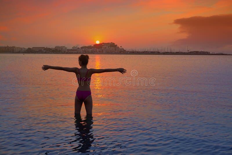Silueta de la muchacha en los brazos abiertos de la puesta del sol de la playa fotografía de archivo libre de regalías