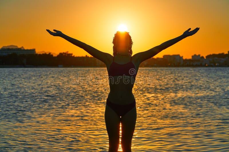 Silueta de la muchacha en los brazos abiertos de la puesta del sol de la playa fotos de archivo