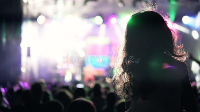 Silueta de la muchacha en los hombros que bailan en el concierto foto de archivo libre de regalías