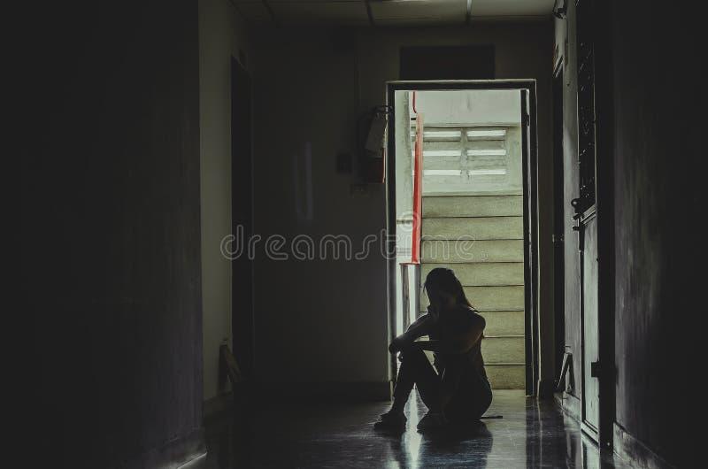 Silueta de la muchacha que se sienta solamente en las mujeres oscuras, tristes y serias que se sientan para abrazar su rodilla so foto de archivo