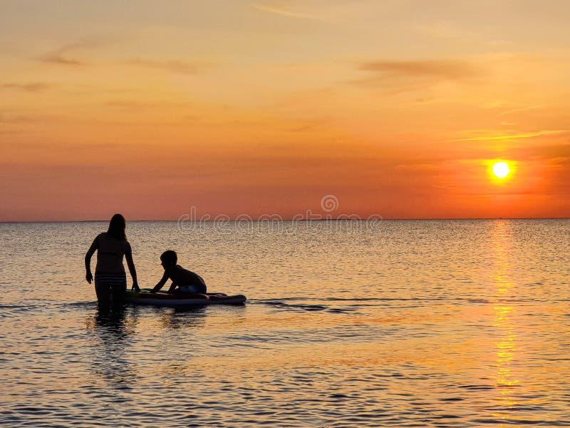 silueta de la muchacha y del niño en la playa en la puesta del sol fotos de archivo libres de regalías