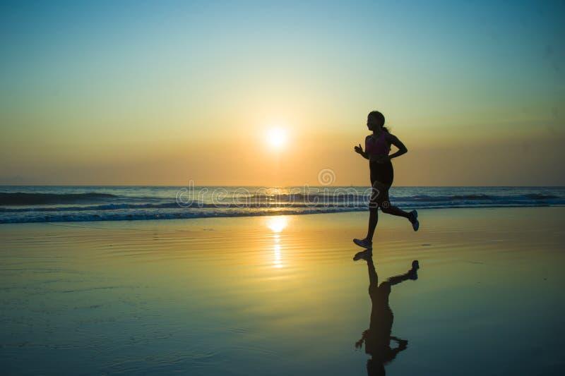 Silueta de la mujer afroamericana feliz y atractiva joven del corredor que ejercita en entrenamiento corriente de la aptitud en e imagen de archivo