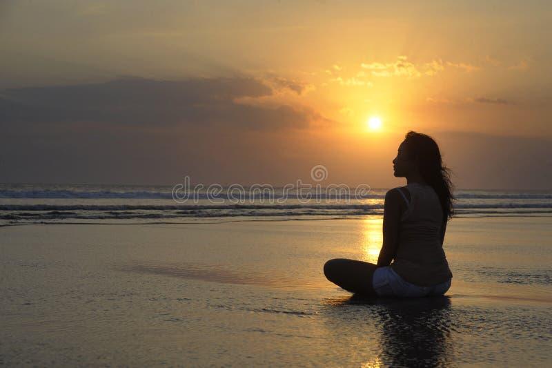 Silueta de la mujer asiática hermosa joven que se sienta en la arena sin agua y relajada mirando el sol en la playa de la puesta  imagen de archivo libre de regalías