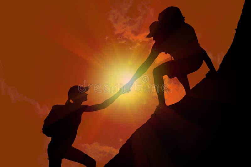Silueta de la mujer de ayuda del hombre a subir en la colina fotos de archivo