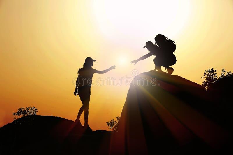 Silueta de la mujer de ayuda del hombre a subir en la colina escarpada fotografía de archivo libre de regalías