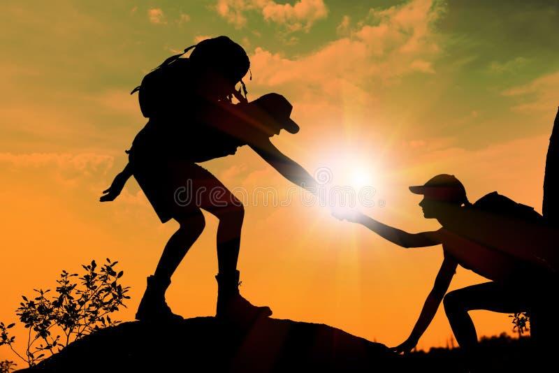 Silueta de la mujer de ayuda del hombre a subir en la colina fotografía de archivo