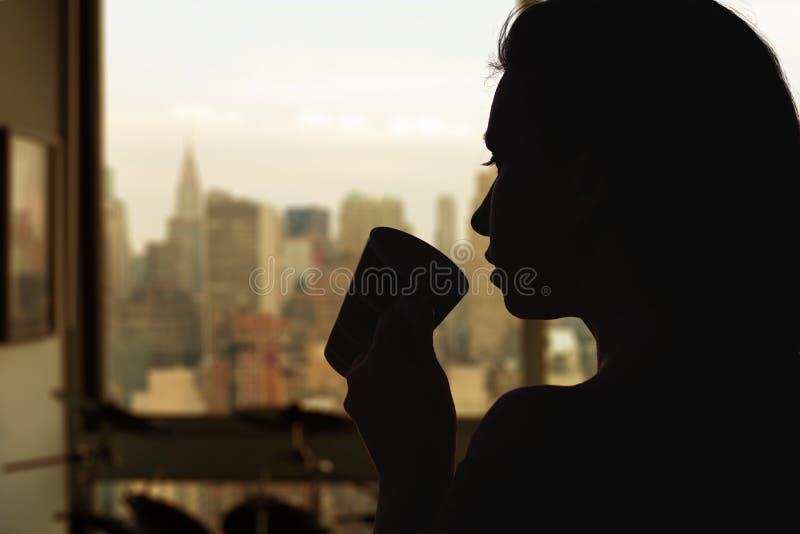 Silueta de la mujer con la taza de té en el apartamento con la opinión de New York City imagen de archivo