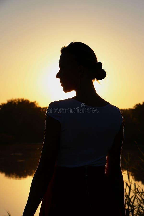Silueta de la mujer en el lado en la puesta del sol fotografía de archivo libre de regalías