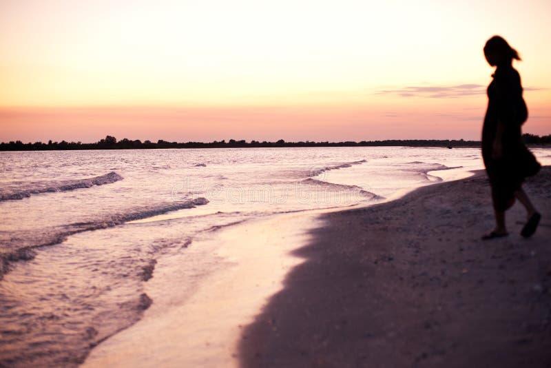 Silueta de la mujer en la costa en la puesta del sol imagenes de archivo