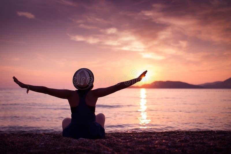 Silueta de la mujer en la playa en la puesta del sol fotos de archivo libres de regalías