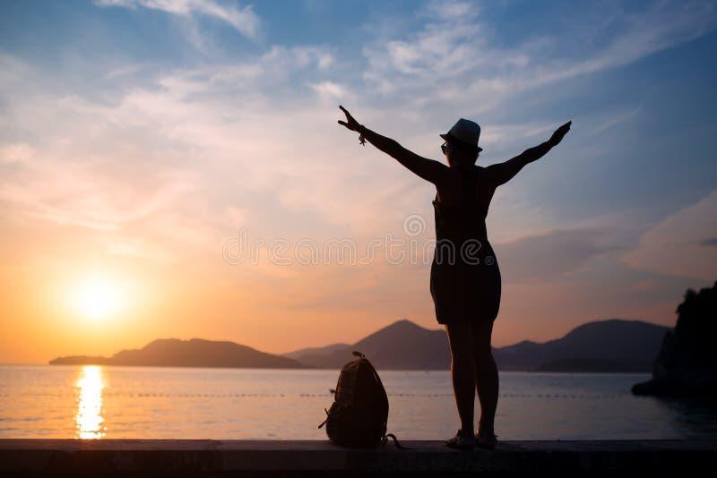 Silueta de la mujer en la playa en la puesta del sol foto de archivo