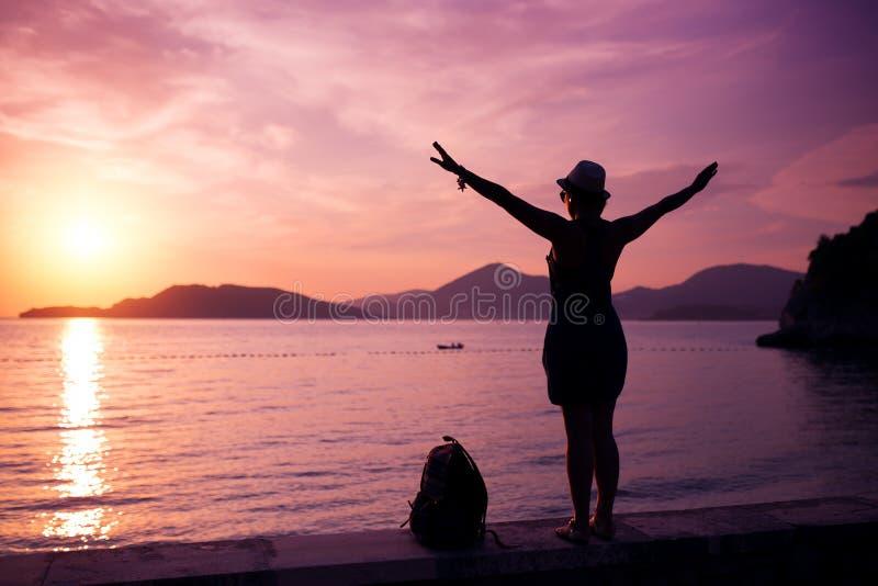 Silueta de la mujer en la playa en la puesta del sol foto de archivo libre de regalías