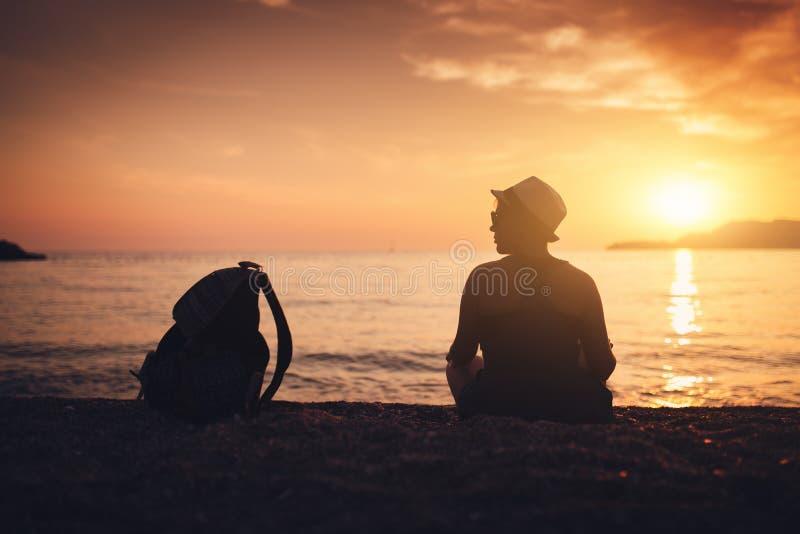 Silueta de la mujer en la playa en la puesta del sol imagen de archivo libre de regalías
