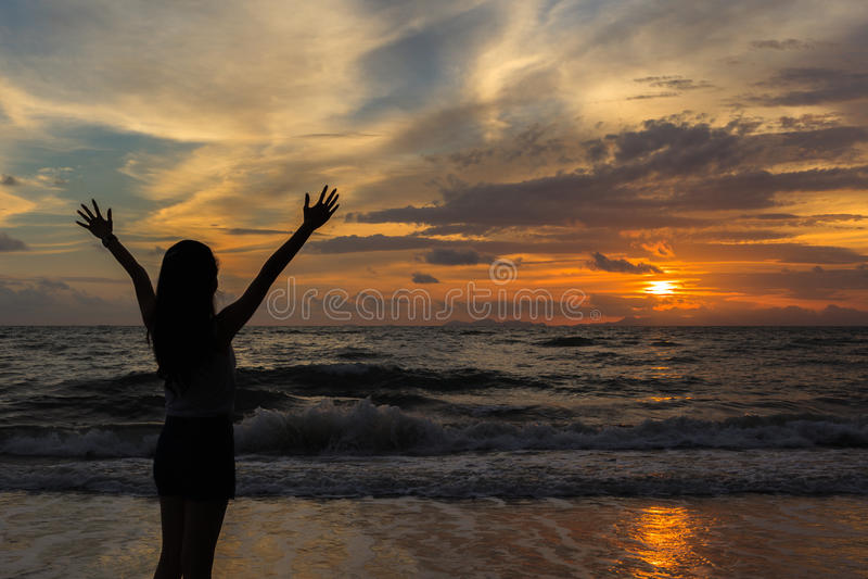 Silueta de la mujer en la puesta del sol imagen de archivo