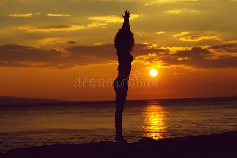 Silueta de la mujer en playa de la puesta del sol fotografía de archivo