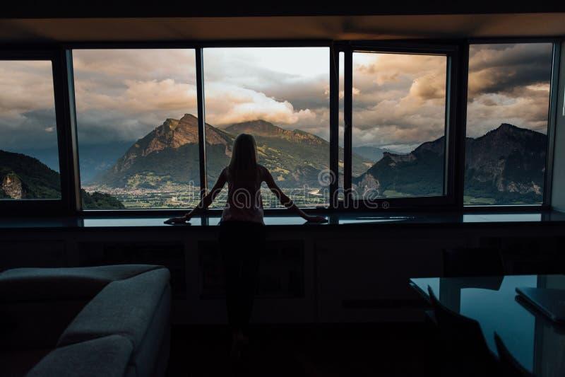 Silueta de la mujer en sol en la ventana con la opinión sobre puesta del sol en montañas fotos de archivo libres de regalías