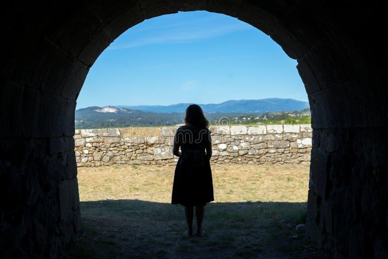 Silueta de la mujer en un túnel de piedra antiguo imagen de archivo libre de regalías