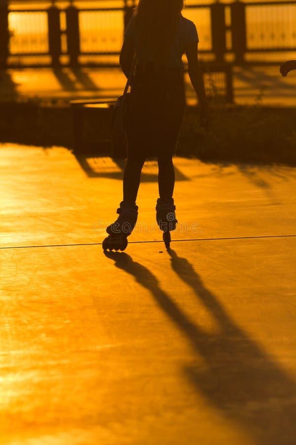 Silueta de la mujer joven en pcteres de ruedas en la 'promenade' en la puesta del sol imagen de archivo