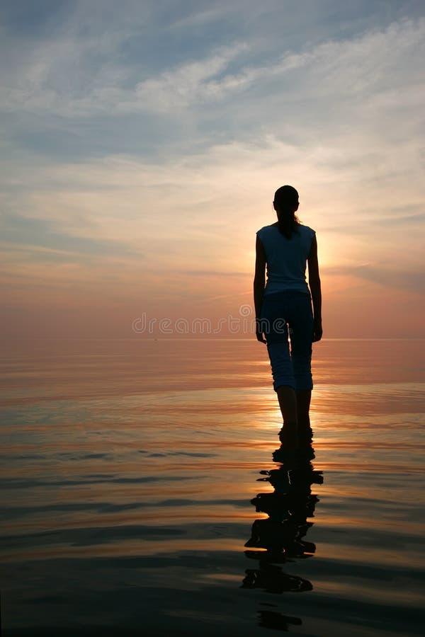 Silueta de la mujer joven que se coloca en un agua foto de archivo
