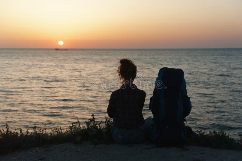 Silueta de la mujer joven que se sienta en la costa con una mochila en el fondo de la puesta del sol imagenes de archivo