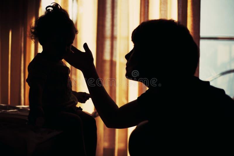 Silueta de la mujer joven y de su niño imagen de archivo libre de regalías