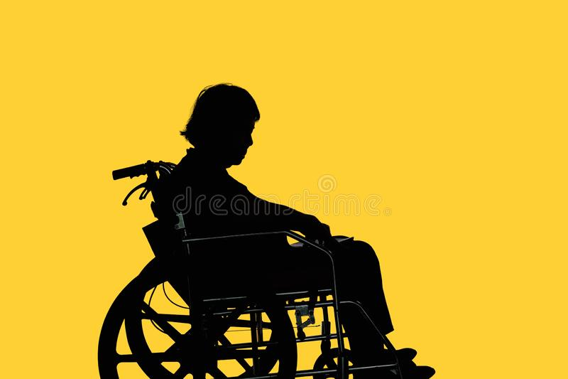 Silueta de la mujer mayor discapacitada que se sienta en su silla de ruedas fotos de archivo libres de regalías