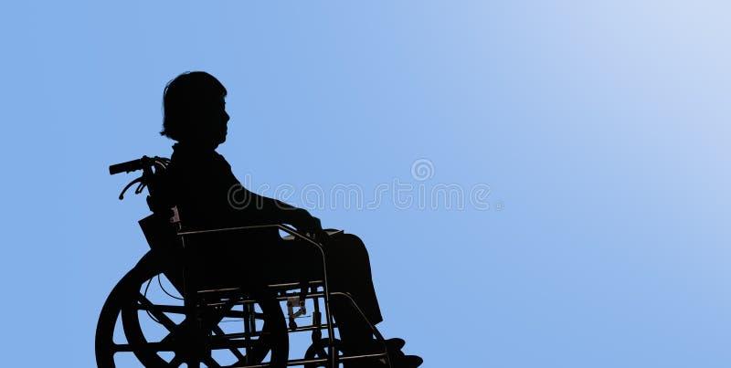 Silueta de la mujer mayor discapacitada que se sienta en su silla de ruedas imágenes de archivo libres de regalías