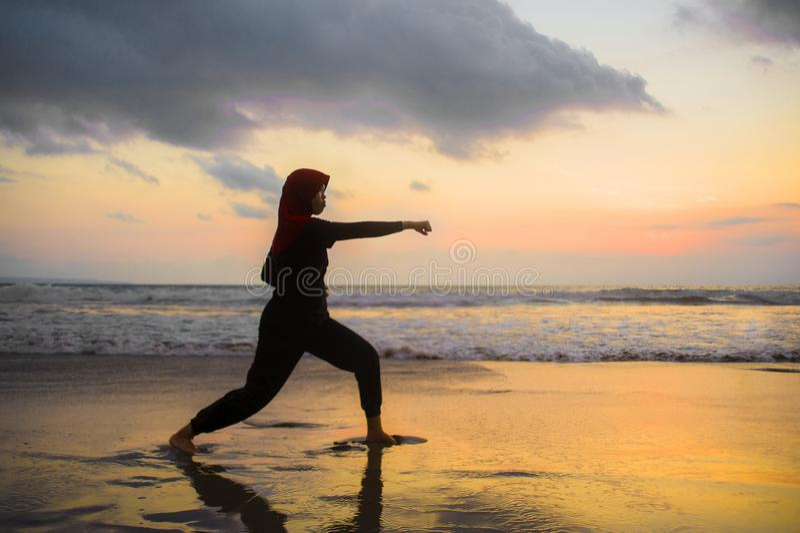 Silueta de la mujer musulmán apta joven cubierta en la bufanda de la cabeza del hijab del Islam que entrena a ataque y a aptitud  foto de archivo libre de regalías
