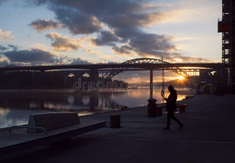Silueta de la mujer que camina en un embarcadero en el amanecer hermoso, temprano imágenes de archivo libres de regalías