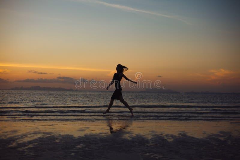 silueta de la mujer que corre en la playa del océano foto de archivo libre de regalías