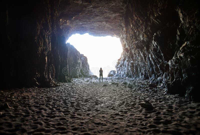 Silueta de la mujer que hace una pausa la salida encendida en cueva foto de archivo