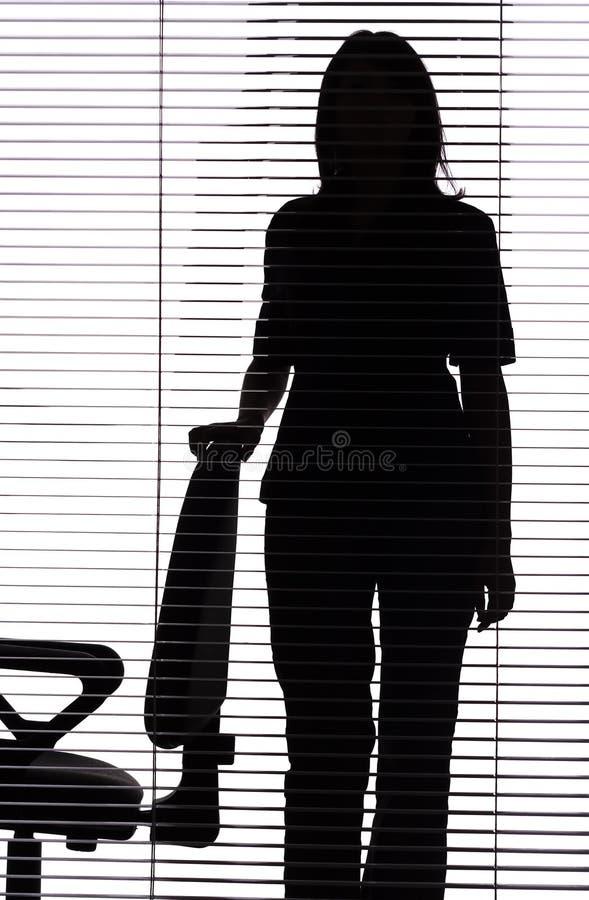 Silueta de la mujer que se coloca al lado de la silla (persianas) fotografía de archivo