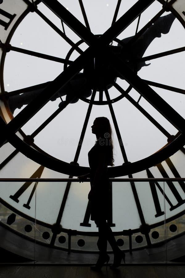Silueta de la mujer que se coloca delante del reloj grande imagen de archivo