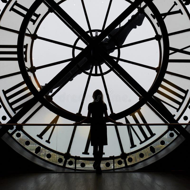 Silueta de la mujer que se coloca delante del reloj grande imagen de archivo libre de regalías