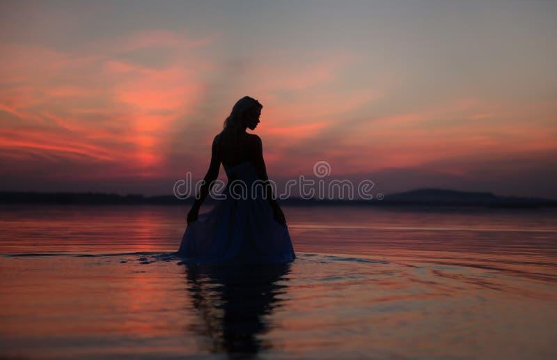 Silueta de la mujer sobre el fondo de la puesta del sol fotos de archivo