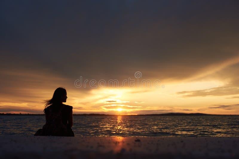 Silueta de la mujer solamente en el borde del agua, disfrutando de paisaje marino hermoso en la puesta del sol imagenes de archivo
