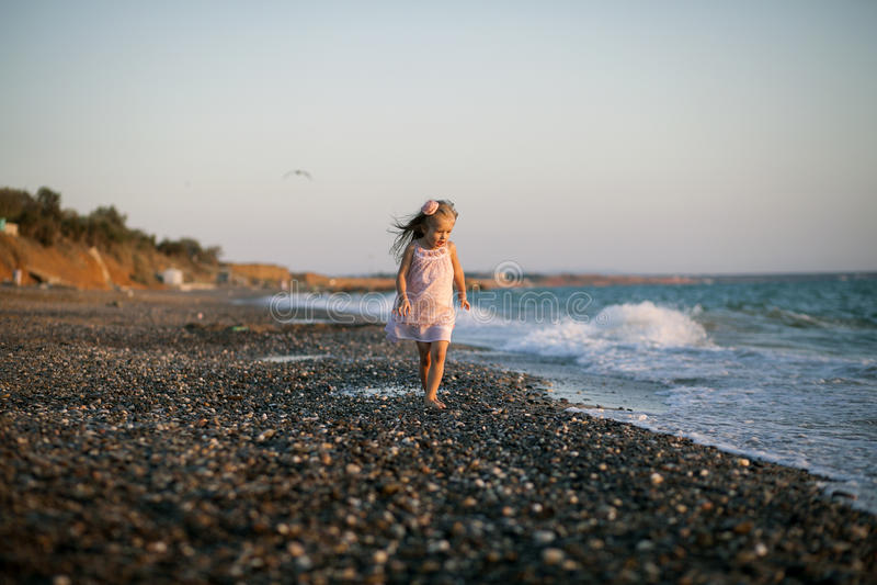Silueta de la niña adorable en una playa en imagen de archivo