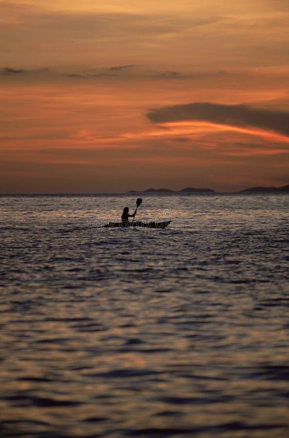 Silueta de la persona kayaking en el mar durante puesta del sol imagen de archivo libre de regalías