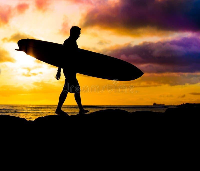 Silueta de la persona que practica surf de la puesta del sol imagen de archivo libre de regalías