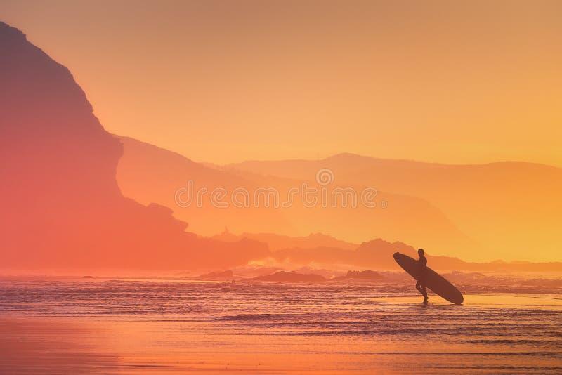 Silueta de la persona que practica surf en la puesta del sol fotografía de archivo libre de regalías