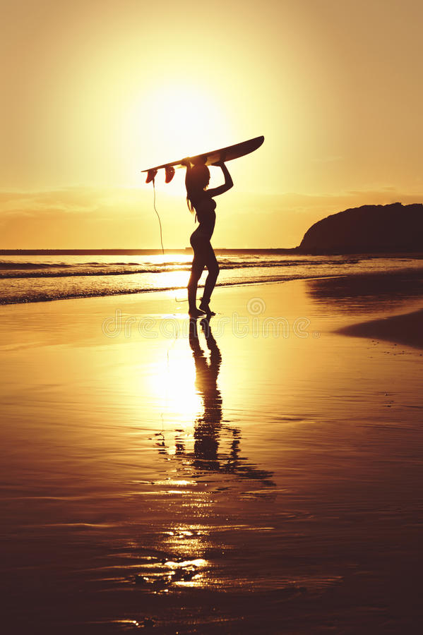 Silueta de la persona que practica surf que se coloca con el tablero de resaca en la playa fotografía de archivo libre de regalías