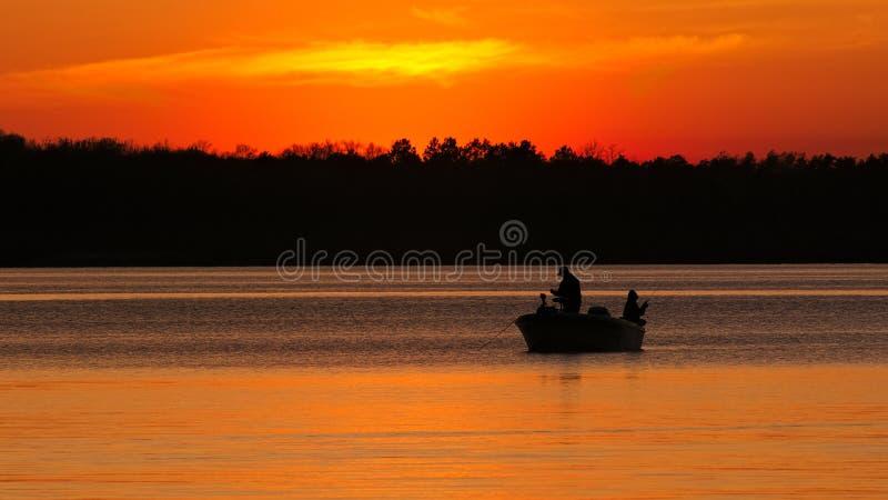 Silueta de la pesca del padre y del hijo en el lago en la puesta del sol imagenes de archivo