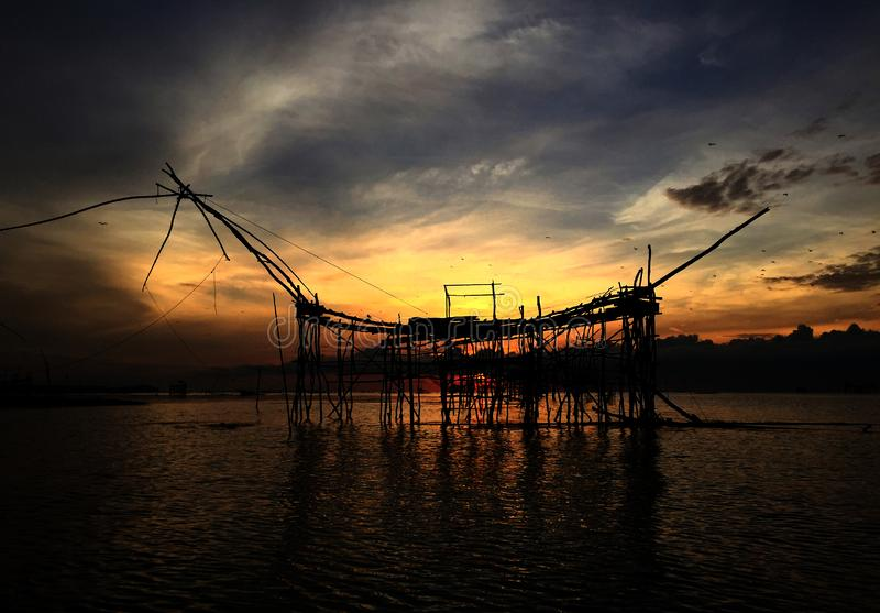 Silueta de la pesca tradicional de la vieja cultura en el lago por la red de inmersión cuadrada de madera en la salida del sol de imágenes de archivo libres de regalías