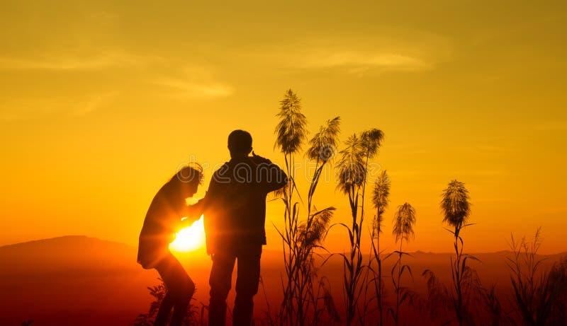 Silueta de la puesta del sol adolescente imagen de archivo