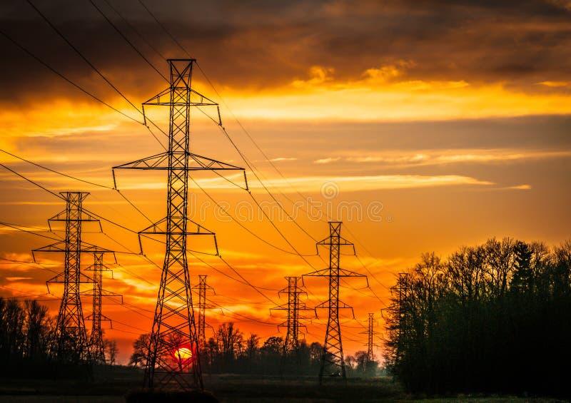 Silueta de la red eléctrica contra un cielo dramático de la puesta del sol imágenes de archivo libres de regalías