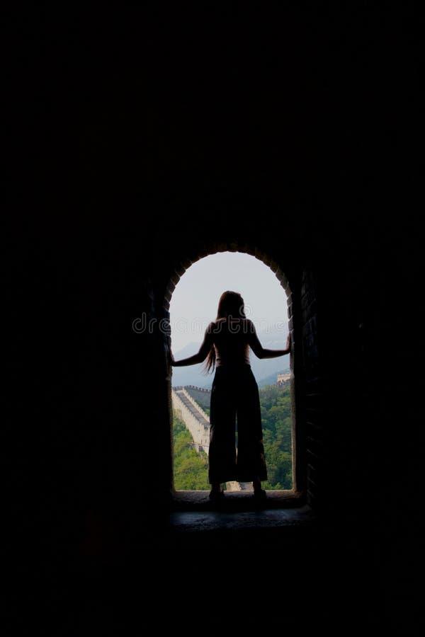 Silueta de la señora de pelo largo en llamaradas contra la Gran Muralla de China imagen de archivo
